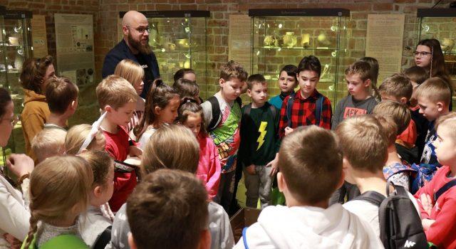 Dyrektor muzeum okręgowego w sandomierzu wraz ze słuchaczami muzealnego uniwersytetu dziecieciego na tle wystawy w sandomierskim muzeum