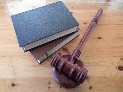 Książki na drewnianym stole oraz młotek sędziowski